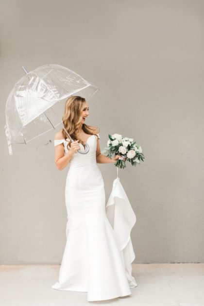 bride holding umbrella - 8 major wedding mistakes brides make and how to avoid them